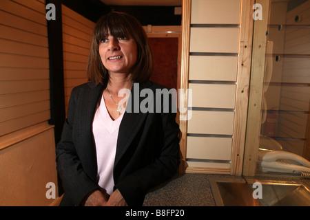 ein Porträt einer mittleren gealterten Business-Frau, die einem Pfandhaus für Gold ausgeführt wird. Sie steht in - Stockfoto