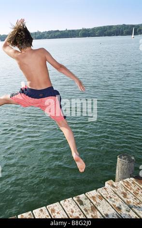 Junge, springen ins Wasser von einer hölzernen Steg - Anrede - Fun - Sommer - schwimmen - Stockfoto