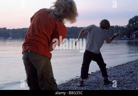 Zwei jungen werfen flache Steinen über die Wasseroberfläche - Schlauheit - Spiel - Freundschaft - See - Dämmerung - Stockfoto