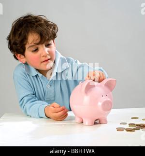junge Münzeinwurf in ein Sparschwein - Stockfoto