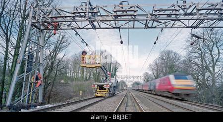 Auftragnehmer auf obenliegende Caternary System hinter teilweise Eisenbahn Blockade, während Züge auf live-Tracks - Stockfoto