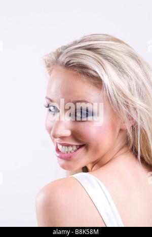 Schöne junge blonde Frau, die über die Schulter schauen - Stockfoto