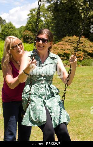 Frauen spielen auf Schaukeln in Hamilton Gardens, New Zealand - Stockfoto