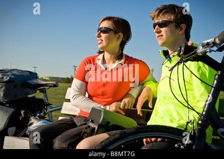 Jung, sitzen auf einer Parkbank neben ihren Touren Fahrräder attraktives Paar. - Stockfoto