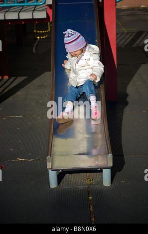 Kleines Mädchen in Winterkleidung Folie in städtischen Spielplatz Rutschen - Stockfoto