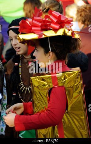 Kleines Mädchen verkleidet als gold Paket vorhanden im roten Band umwickelt. Ein Kandidat in jährlichen Karneval - Stockfoto