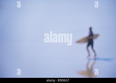 Abstrakte Surfer mit Surfbrett am Strand - Stockfoto