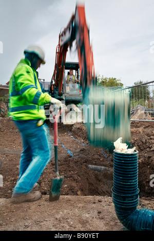 Arbeiter schaut zu, wie Jcb Graben gräbt - Stockfoto
