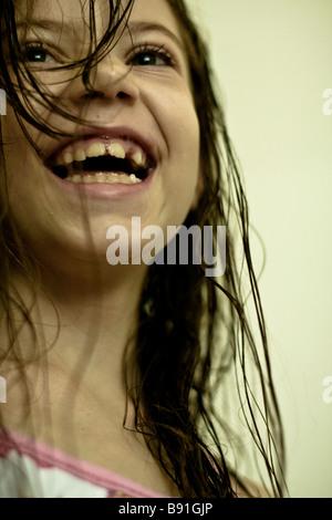 8 Jahre altes Mädchen, das ein natürliches Lächeln und mit nassen Haaren versaut