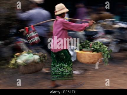 Kambodscha Siem Reap verschwommen Aktion bewegte Frau tragen frisch produzieren in zwei Körben balanciert auf einem - Stockfoto