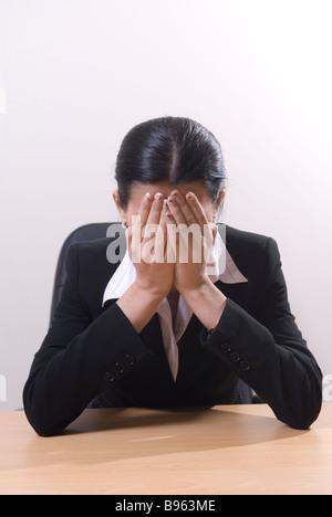Business-Frau saß im Büro Weinen Kopf in Händen - Stockfoto