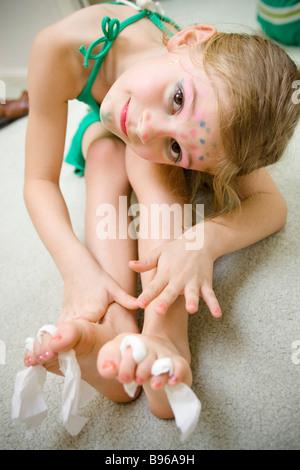 Ein junges Mädchen zeigt ihre frisch lackierten Nägel stolz - Stockfoto