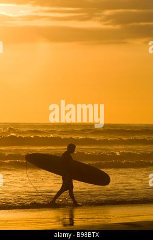 Surfer mit seinem Surfbrett entlang des Ozeans bei Sonnenuntergang in Dominical, Costa Rica. - Stockfoto