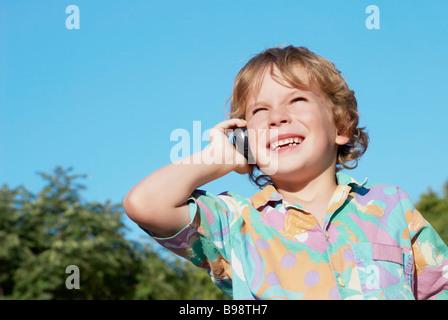 Der fröhliche junge mit einem Mobiltelefon im park - Stockfoto