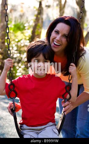 Hispanische Mutter und Sohn Spaß im Freien im Park auf Schaukel und lachen - Stockfoto