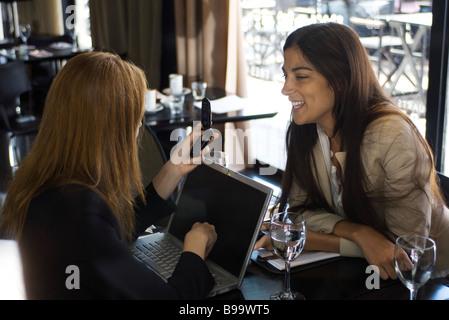 Zwei junge Frauen sitzen im Café, im Chat, eine Verwendung von Laptop und Handy - Stockfoto