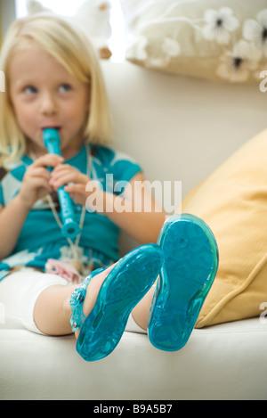 Kleines Mädchen sitzt auf dem Sofa, Blockflöte zu spielen - Stockfoto