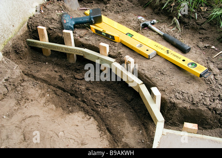 Die Fußnoten sind für eine kleine gebogene Gartenmauer heraus gegraben worden sind und die Schalung aus 2 x 1 im - Stockfoto