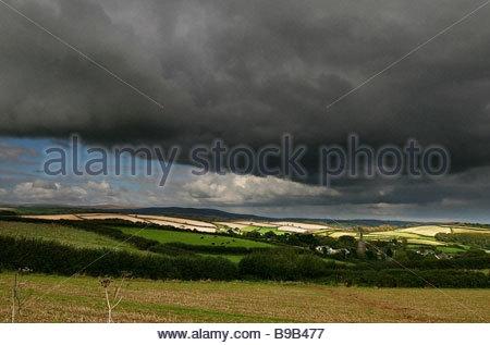 Ein Sommergewitter rollt sich einem kleinen Dorf namens Holbeton, bevor es Richtung Dartmoor National Park Köpfe. - Stockfoto