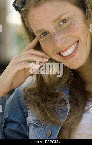 Junge Frau mit Sommersprossen lächelnd in die Kamera, Porträt - Stockfoto