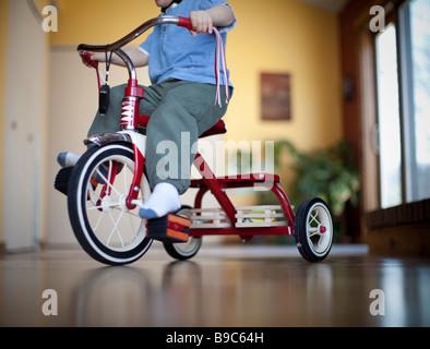 Kleinkind Reiten ein Dreirad rund um das Haus - Stockfoto