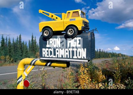 Eisenzeit Reclamation Business Firmenschild auf ländlichen Mailbox mit recycelten Spielzeug Abschleppwagen an der - Stockfoto