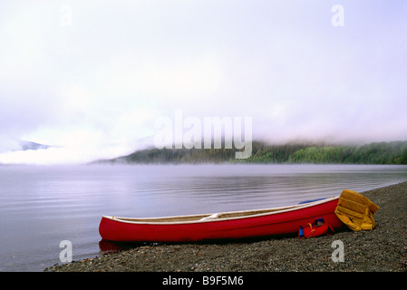 Kanu am Strand am Bowron Lake am nebligen Morgen im Bowron Lake Provincial Park in der Cariboo Region British Columbia - Stockfoto