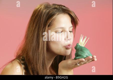 Frau junge spürbare Kunststoff-Frosch Krone küsst Porträt-Serie Menschen Mädchen Teenager Jugendliche 17-20 Jahre - Stockfoto