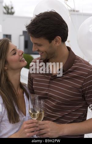 Mate Lächeln auf den Lippen liebevoll schaut Sektgläser Champagner-Gläser feiert vor 20-30 Jahre 30-40 Jahre betrachten - Stockfoto