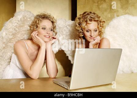 Frauen junge blonde Engelsflügel fröhlich lächelnd Träume Weg in Gedanken Laptop Tisch semi-Porträt Weihnachten - Stockfoto