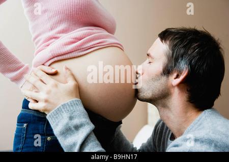 Mann küssen Frau schwanger Bauch - Stockfoto