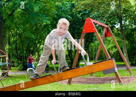 Junge, sechs Jahre, Klettern auf einer Wippe - Stockfoto