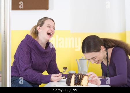 Zwei junge Frauen am Tisch, lachen - Stockfoto
