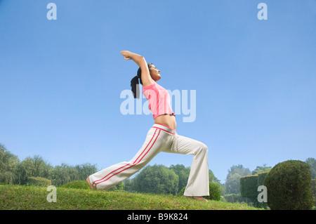 Frau Krieger 1 Pose des Yoga in einem Park zu üben - Stockfoto