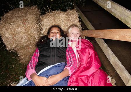 Mädchen in Schlafsäcken auf haybales - Stockfoto