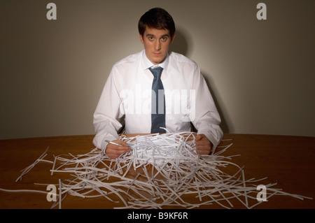 Geschäftsmann mit Haufen von Papierschnitzel auf seinem Schreibtisch - Stockfoto