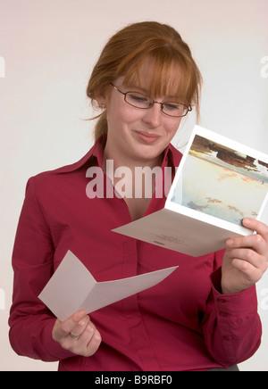 Eine Frau liest eine Karte, die einige frohe Botschaft übermittelt hat, die ihr Lächeln gemacht hat - Stockfoto