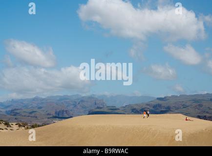 Touristen zu Fuß auf den Dünen in Maspalomas mit den Bergen von Gran Canaria in der Ferne - Stockfoto