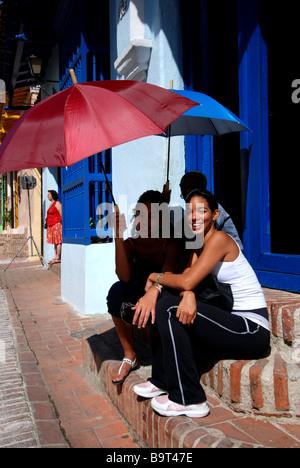 Junge Frau, die Standortwahl auf Treppe mit Sonnenschirme für Schatten Stadt Camagüey, Kuba - Stockfoto