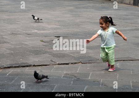 Kleines Mädchen jagt eine Taube an der Kathedrale Guadalupe, Mexiko-Stadt - Stockfoto