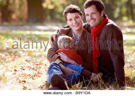 Ein Porträt einer jungen Familie sitzen auf dem Rasen im Herbst - Stockfoto