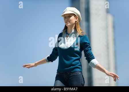 Junge Frau, die trendigen Hut trägt, steht im Freien mit Armen - Stockfoto