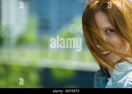 Junge rote kurzhaarige Frau mit Haaren weht über Gesicht, Porträt - Stockfoto