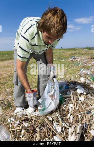 Männliche Abholung Müll im Bereich - Stockfoto