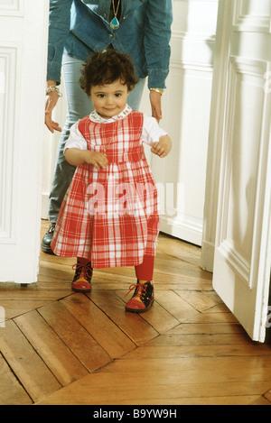 Kleine Mädchen gehen, Mutter nach hinten