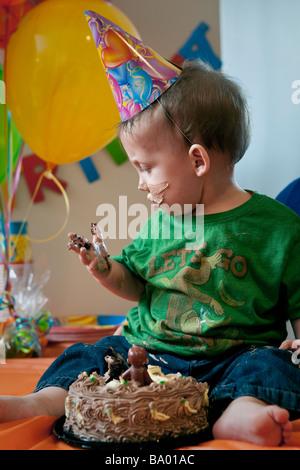 Ein kleiner Junge schaut auf seine Hand bedeckt mit Kuchen während der Geburtstagsfeier. - Stockfoto