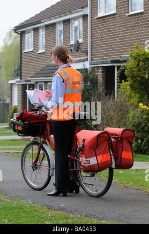 Royal Mail Briefträgerin sortieren Briefe auf ihrer Runde - Stockfoto