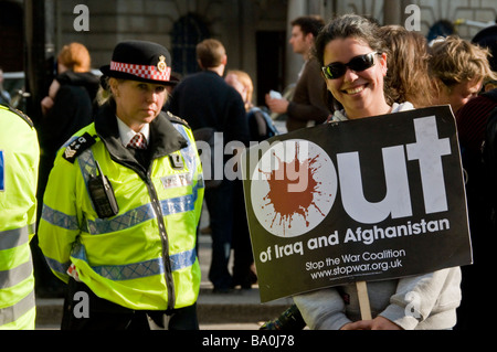 Ein junges Mädchen Demonstrant posiert mit einer Anti-Kriegs-Banner und eine Polizistin im Hintergrund, G20-Gipfel - Stockfoto