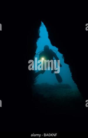 Silhouette Taucher leuchtende Taschenlampe in eine Höhle aus der Channel Islands Nationalpark Insel Santa Cruz, - Stockfoto