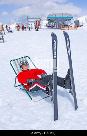 ein Teenager ruht in einem Leinwand Stuhl auf der Reiteralm in der Steiermark, im Hintergrund Dachstein Gebirge, - Stockfoto